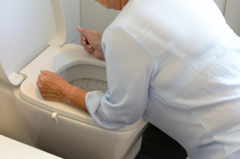 Γυναίκα που αρρωσταίνει πέρα από ένα κύπελλο τουαλετών στοκ φωτογραφίες με δικαίωμα ελεύθερης χρήσης