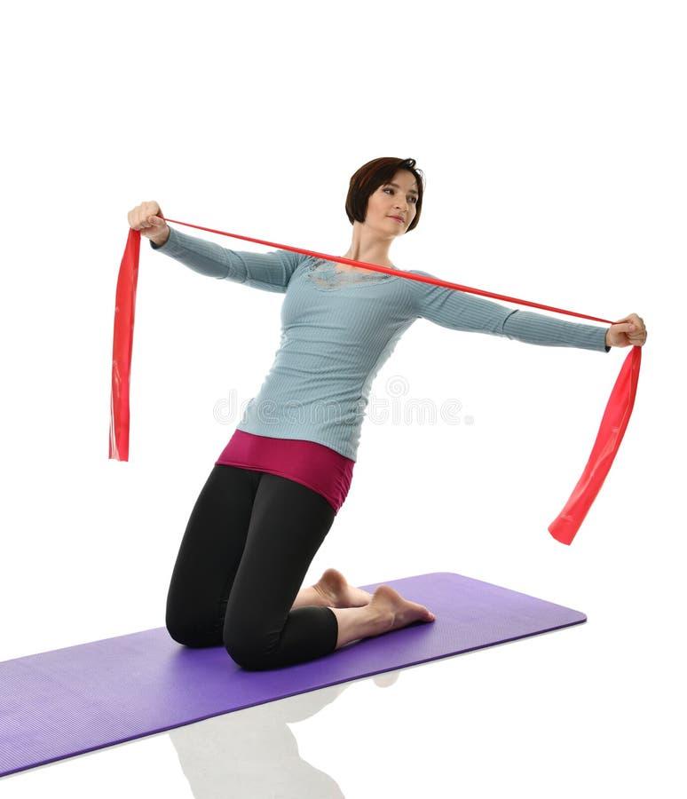 Γυναίκα που ασκεί κάνοντας το μεταγεννητικό workout Θηλυκός εκπαιδευτικός ικανότητας την κόκκινη λαστιχένια ζώνη αντίστασης που α στοκ φωτογραφία με δικαίωμα ελεύθερης χρήσης