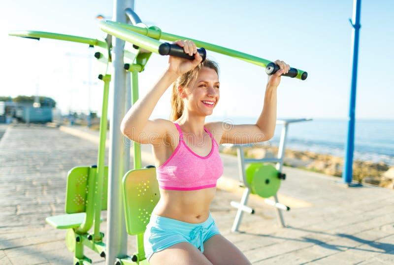 Γυναίκα που ασκεί με τον εξοπλισμό άσκησης στο δημόσιο πάρκο από το τ στοκ εικόνες