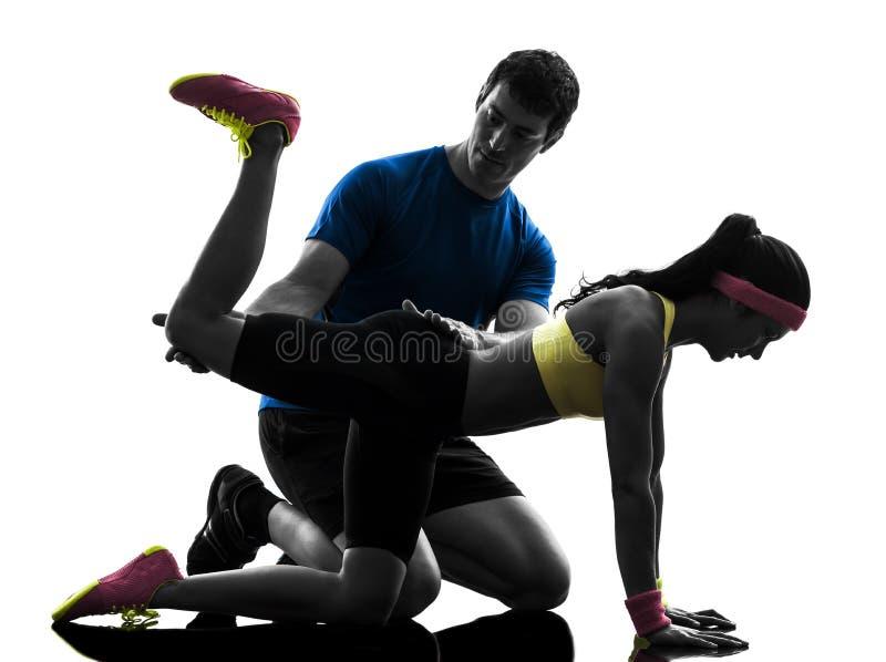 Γυναίκα που ασκεί την ικανότητα θέσης σανίδων workout με το λεωφορείο ανδρών στοκ φωτογραφία με δικαίωμα ελεύθερης χρήσης
