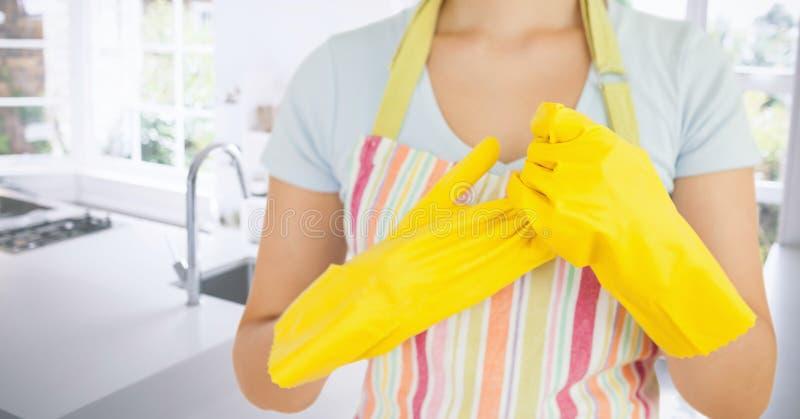 Γυναίκα που αφαιρεί τα λαστιχένια γάντια στην κουζίνα στοκ φωτογραφία με δικαίωμα ελεύθερης χρήσης