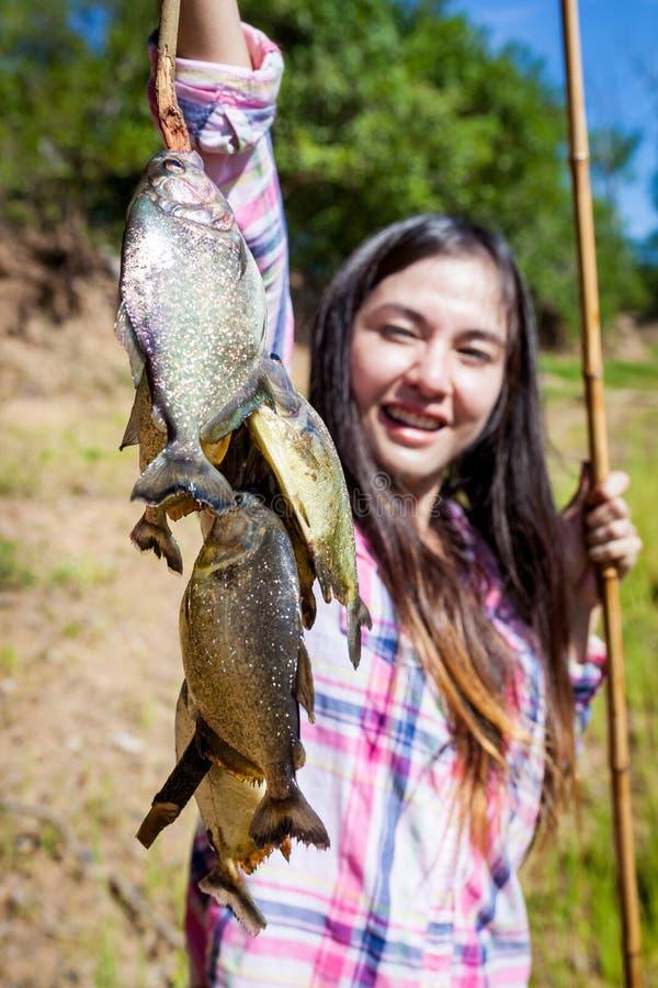 Γυναίκα που αλιεύει Piranha στοκ εικόνες