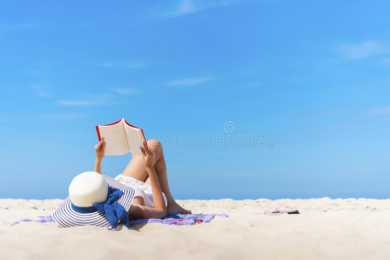 Γυναίκα που βάζει και που διαβάζει στην παραλία με το μπλε ουρανό στους θερινούς χρόνους στοκ φωτογραφίες