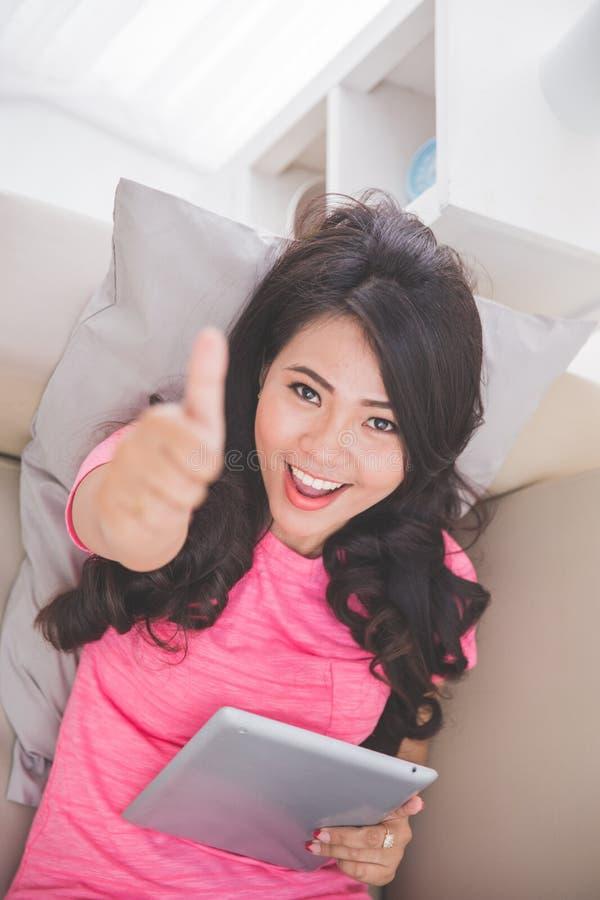 Γυναίκα που βάζει σε έναν καναπέ που χρησιμοποιεί ένα PC ταμπλετών που παρουσιάζει αντίχειρα στοκ εικόνες