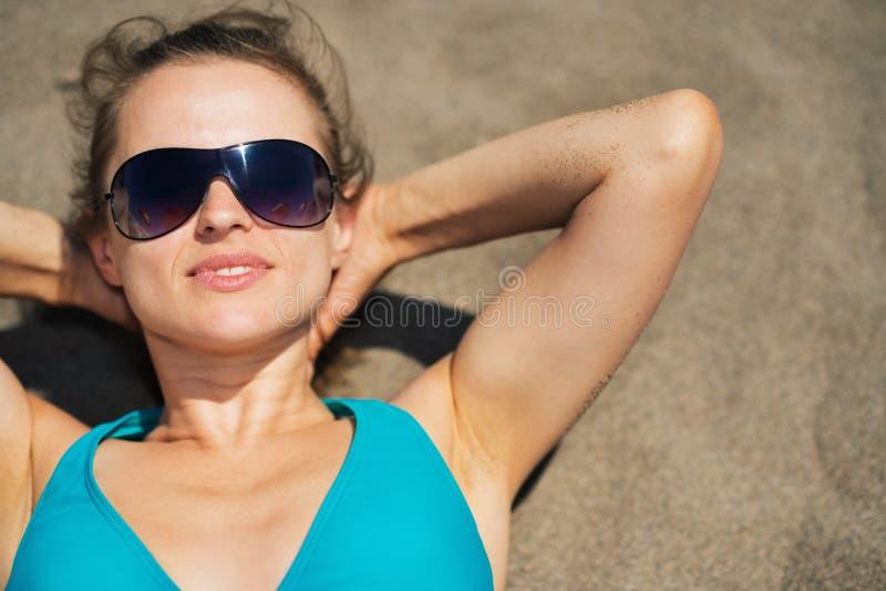 Γυναίκα που βάζει στην άμμο παραλιών στοκ φωτογραφία