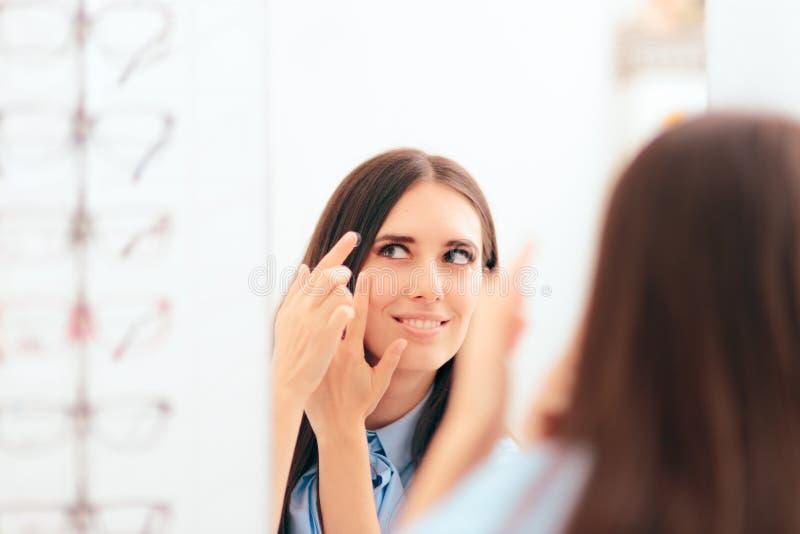 Γυναίκα που βάζει στους ιατρικούς φακούς επαφής στον καθρέφτη στοκ φωτογραφίες