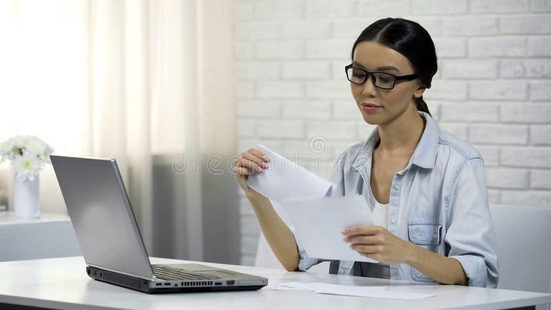 Γυναίκα που βάζει την επιστολή στη συνεδρίαση φακέλων στο σπίτι, που συμπληρώνει τη φορολογική δήλωση στοκ φωτογραφίες με δικαίωμα ελεύθερης χρήσης