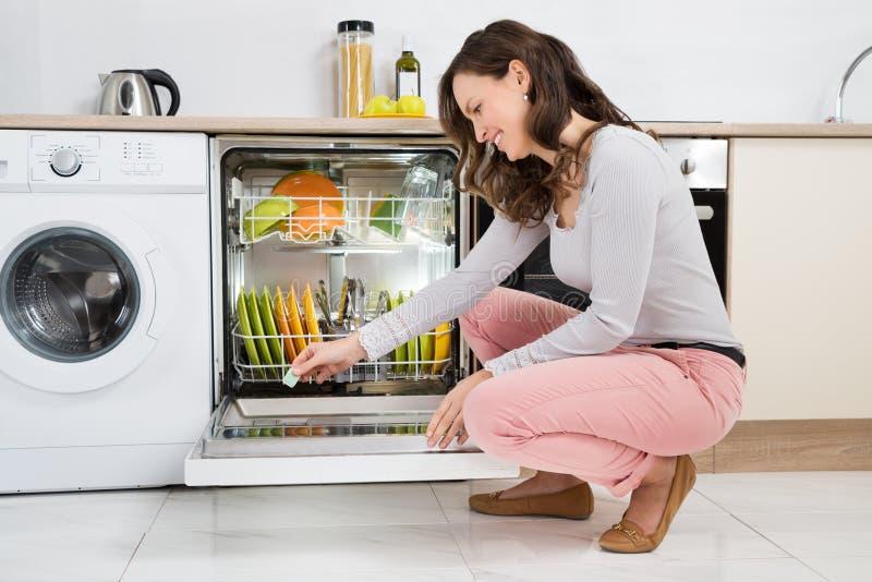 Γυναίκα που βάζει την καθαριστική ταμπλέτα στο πλυντήριο πιάτων στοκ φωτογραφίες με δικαίωμα ελεύθερης χρήσης