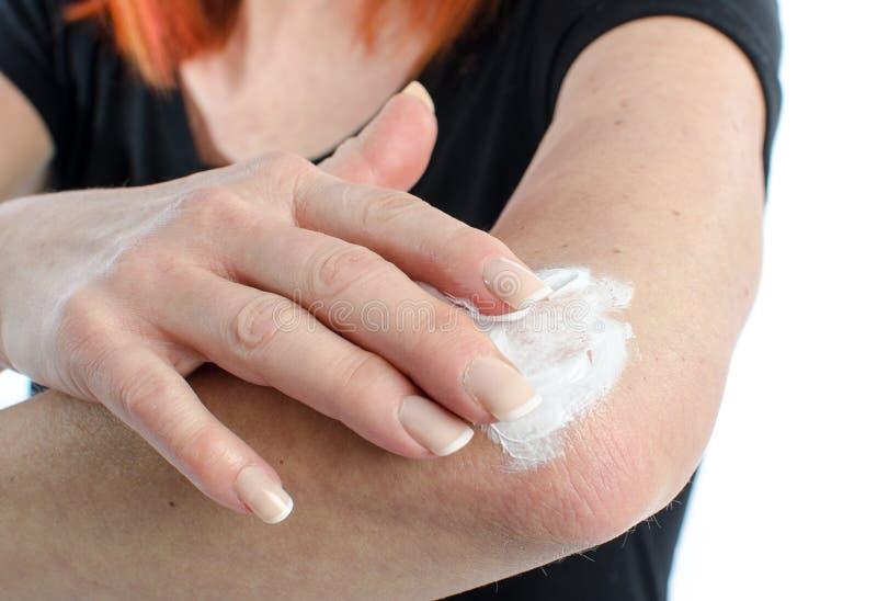 Γυναίκα που βάζει την κρέμα στον αγκώνα της στοκ φωτογραφία με δικαίωμα ελεύθερης χρήσης