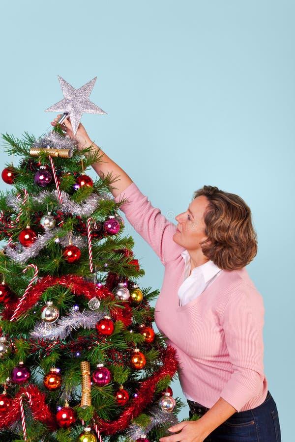 Γυναίκα που βάζει το αστέρι πάνω από το χριστουγεννιάτικο δέντρο στοκ εικόνα με δικαίωμα ελεύθερης χρήσης