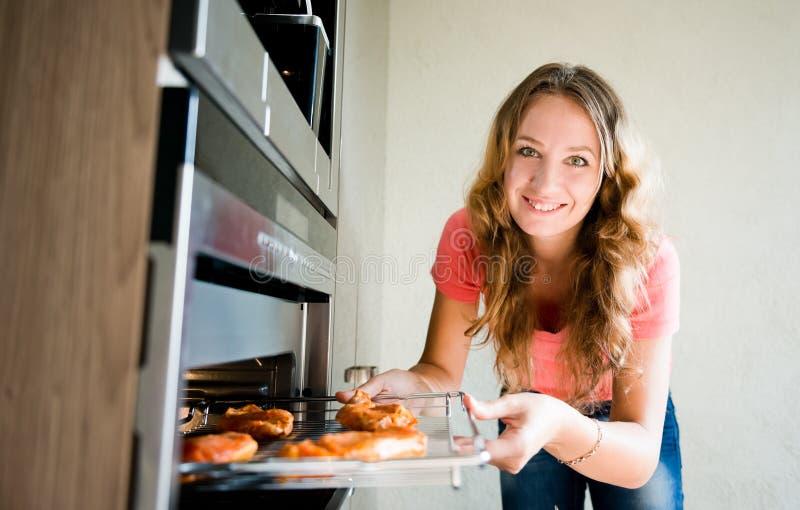 Γυναίκα που βάζει το κρέας στο φούρνο στοκ φωτογραφία με δικαίωμα ελεύθερης χρήσης