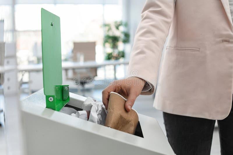 Γυναίκα που βάζει το χρησιμοποιημένο φλυτζάνι εγγράφου στο δοχείο απορριμμάτων στο σύγχρονο γραφείο Ανακύκλωση αποβλήτων στοκ εικόνες με δικαίωμα ελεύθερης χρήσης