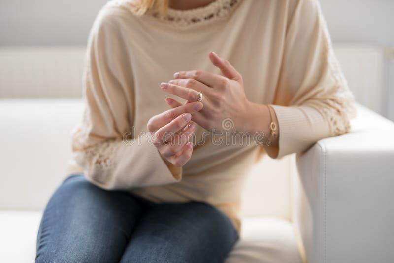 Γυναίκα που βγάζει το γαμήλιο δαχτυλίδι της στοκ εικόνες