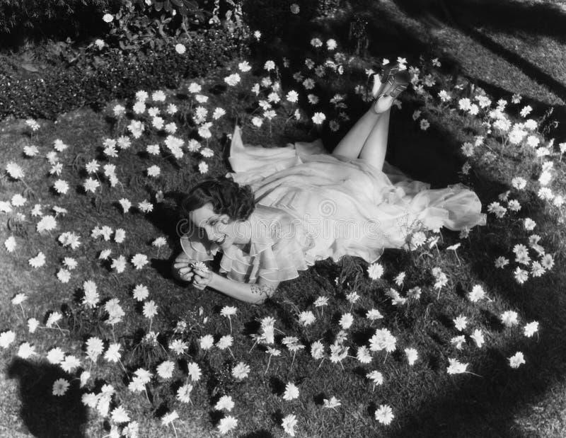 Γυναίκα που βρίσκεται στη χλόη που περιβάλλεται από τα λουλούδια (όλα τα πρόσωπα που απεικονίζονται δεν ζουν περισσότερο και κανέ στοκ εικόνα