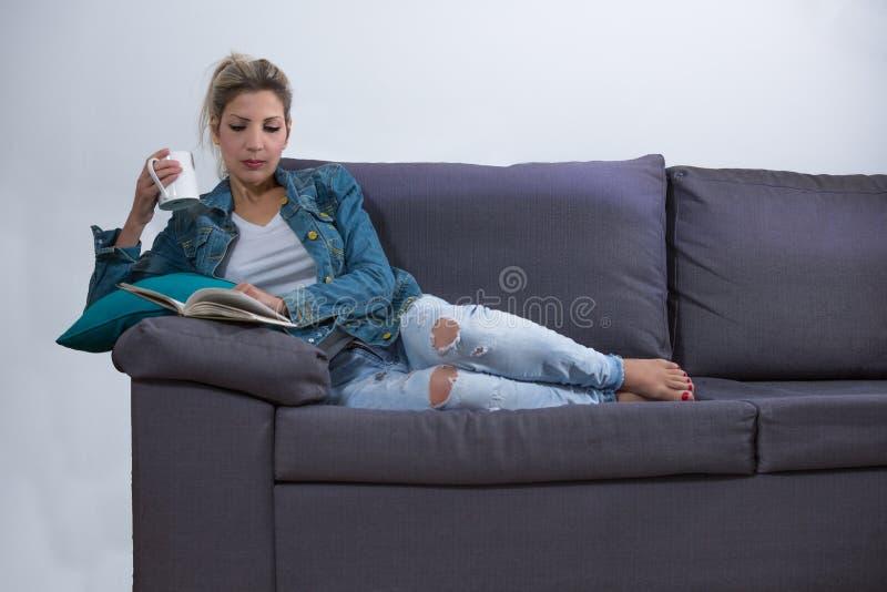 Γυναίκα που βρίσκεται στον καναπέ με ένα φλιτζάνι του καφέ και ένα βιβλίο στοκ εικόνα με δικαίωμα ελεύθερης χρήσης