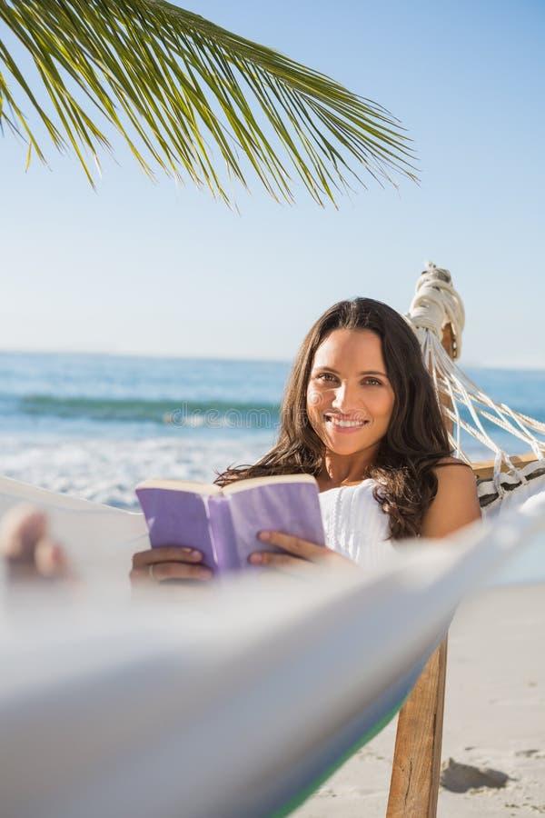 Γυναίκα που βρίσκεται στο βιβλίο εκμετάλλευσης αιωρών και που χαμογελά στη κάμερα στοκ εικόνα