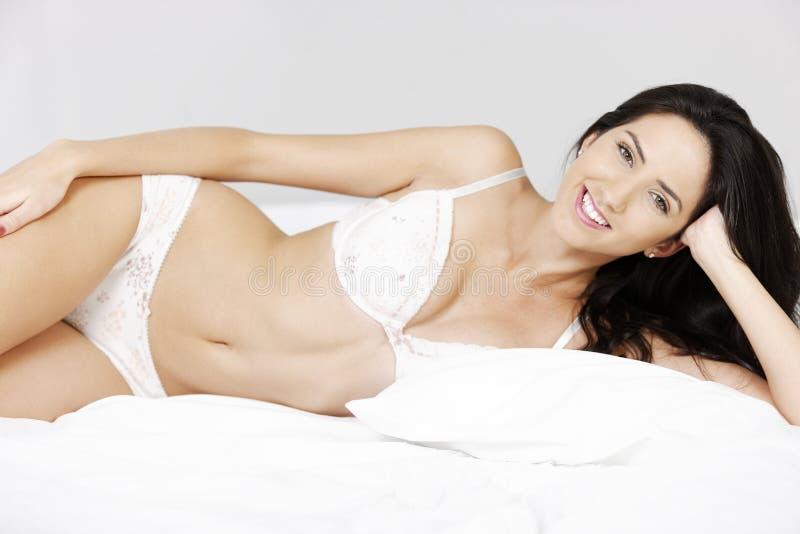 Γυναίκα που βρίσκεται στο κρεβάτι στοκ φωτογραφίες