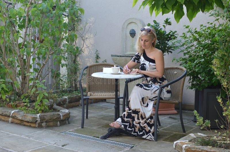 Γυναίκα που γράφει σε έναν κήπο στοκ εικόνες