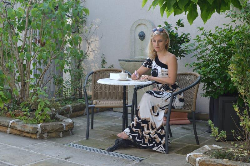 Γυναίκα που γράφει σε έναν κήπο στοκ φωτογραφία