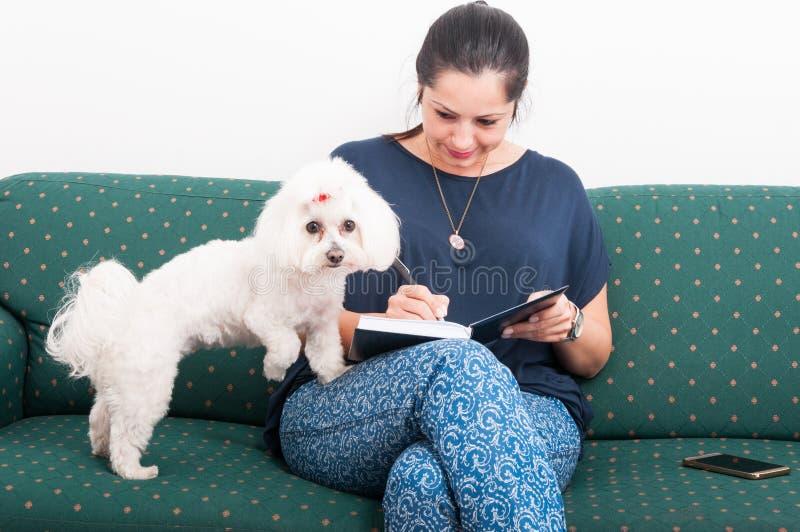 Γυναίκα που γράφει στο σημειωματάριο και που κάθεται στον καναπέ στοκ εικόνες