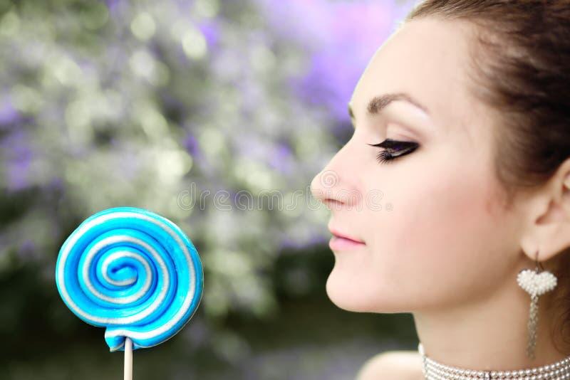 Γυναίκα που γλείφει ένα μπλε λαμπρό lollipop κοντά επάνω στο κλίμα φύσης στοκ εικόνες