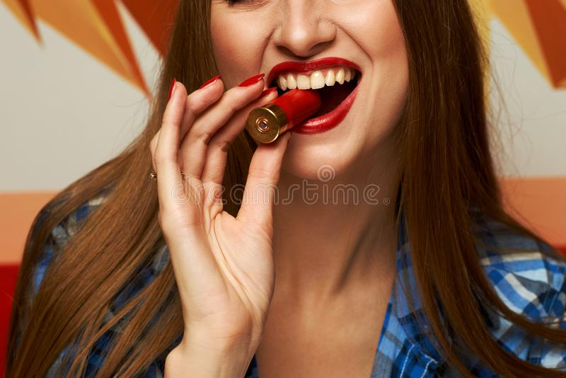 Γυναίκα που δαγκώνει το κόκκινο κοχύλι κυνηγετικών όπλων στοκ φωτογραφία