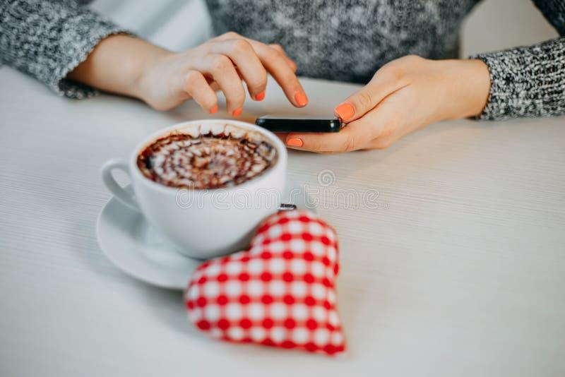 Γυναίκα που δακτυλογραφεί ένα μήνυμα στο βαλεντίνο της που περιμένει στον καφέ Valenti στοκ εικόνες