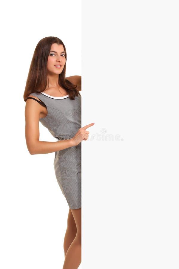 Γυναίκα που δείχνει στο λευκό σημαδιών πινάκων διαφημίσεων στοκ φωτογραφίες με δικαίωμα ελεύθερης χρήσης