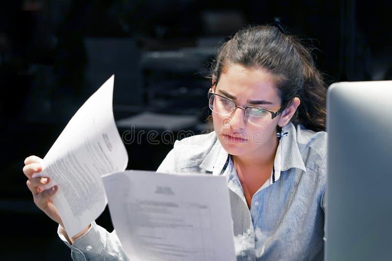 Γυναίκα που διαβάζει ένα έγγραφο στο χώρο εργασίας γραφείων στοκ φωτογραφίες με δικαίωμα ελεύθερης χρήσης