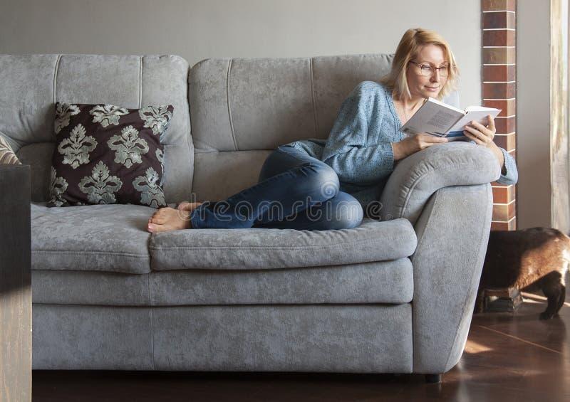 Γυναίκα που διαβάζει ένα βιβλίο στον καναπέ στοκ εικόνες με δικαίωμα ελεύθερης χρήσης