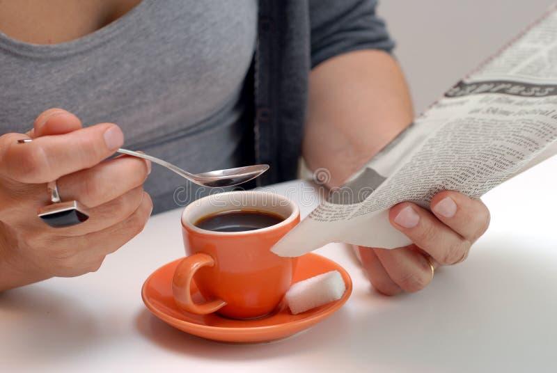 Γυναίκα που διαβάζει την εφημερίδα της ενώ έχοντας έναν καφέ απεικόνιση αποθεμάτων
