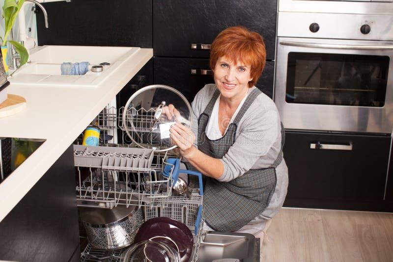Γυναίκα που διπλώνει τα πιάτα στο πλυντήριο πιάτων στοκ φωτογραφία