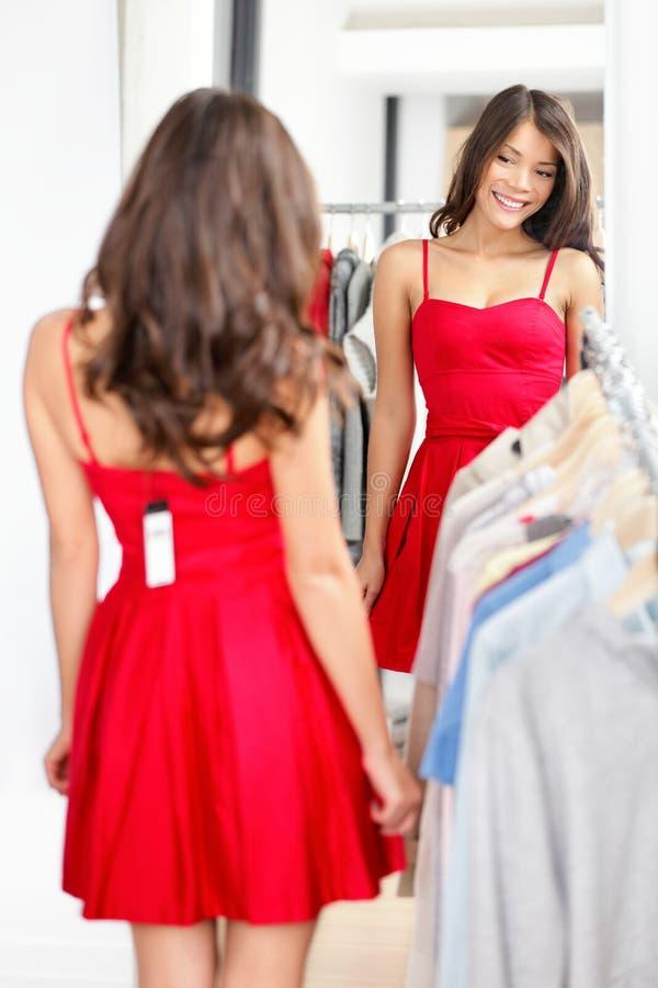 Γυναίκα που δοκιμάζει το φόρεμα στοκ φωτογραφία