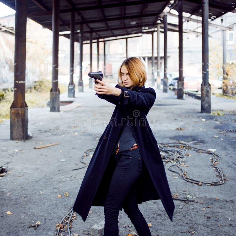 Γυναίκα που δείχνει ένα πυροβόλο όπλο Πυροβολισμός κοριτσιών μαφίας σε κάποιο στην οδό στοκ φωτογραφία με δικαίωμα ελεύθερης χρήσης