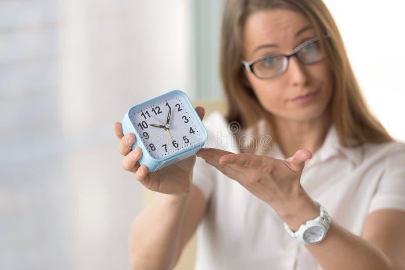 Γυναίκα που δείχνει στο χρόνο, εστίαση στο ρολόι, ακρίβεια προθεσμίας con στοκ εικόνα