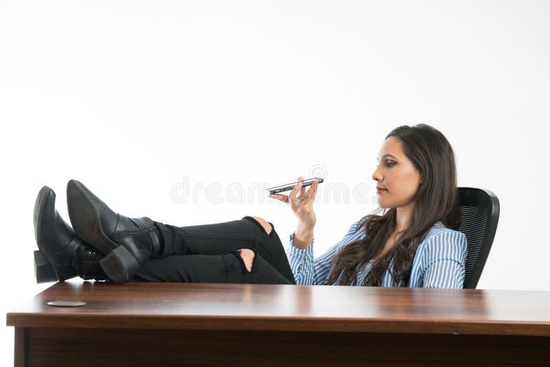Γυναίκα που ελέγχει εάν το κινητό τηλέφωνο είναι εντάξει στο γραφείο, καθμένος με το λ στοκ φωτογραφία