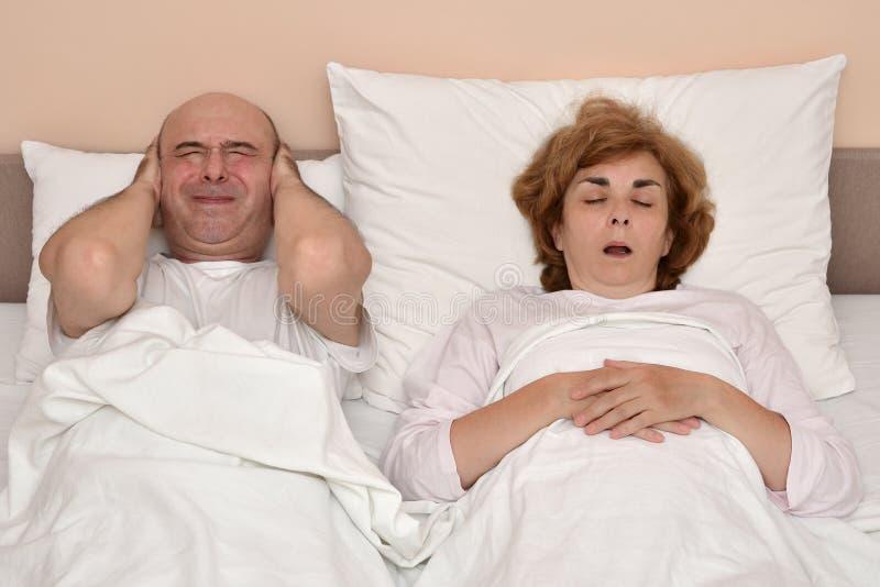 Γυναίκα που ενώ ο άνδρας δεν μπορεί να κοιμηθεί στοκ εικόνα με δικαίωμα ελεύθερης χρήσης