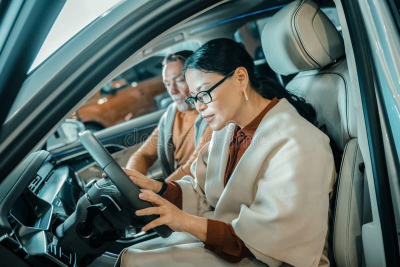 Γυναίκα που εξερευνά το αυτοκίνητο στην αίθουσα εκθέσεως στοκ φωτογραφία