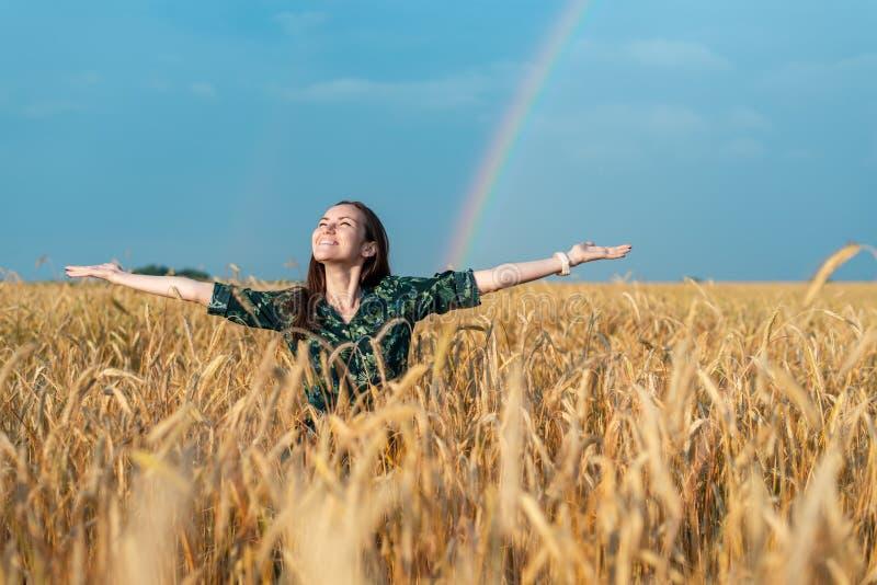 Γυναίκα που εξετάζει επάνω τα χέρια ουρανού στην πλευρά σε έναν τομέα με τα δημητριακά σε ένα υπόβαθρο ουράνιων τόξων στοκ εικόνες
