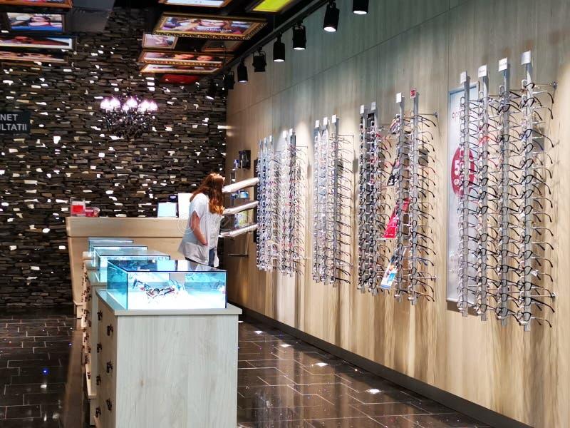 Γυναίκα που εξετάζει τα γυαλιά eyeglass στο κατάστημα Optiplaza στοκ εικόνα με δικαίωμα ελεύθερης χρήσης