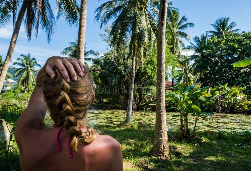 Γυναίκα που εξετάζει την όμορφη τροπική άποψη με τους φοίνικες και τη μικρή λίμνη στοκ εικόνα