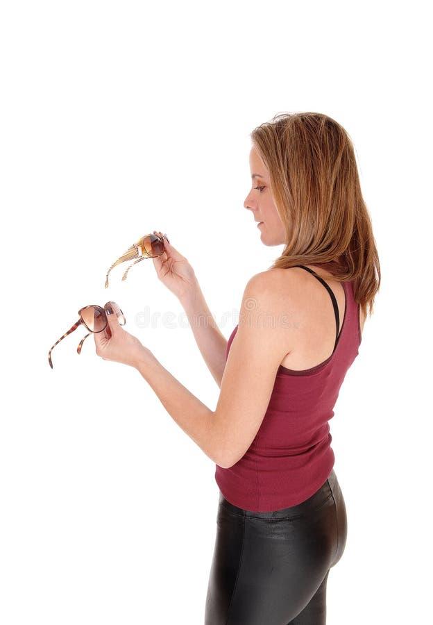 Γυναίκα που εξετάζει τη μάγισσα γυαλιών ηλίου για να αγοράσει στοκ εικόνες με δικαίωμα ελεύθερης χρήσης