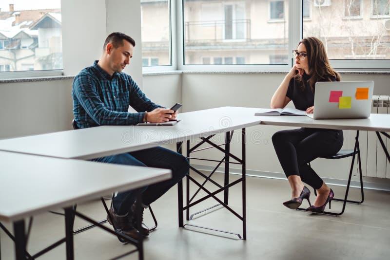 Γυναίκα που εξετάζει τον άνδρα συνάδελφός της στο γραφείο στοκ εικόνες
