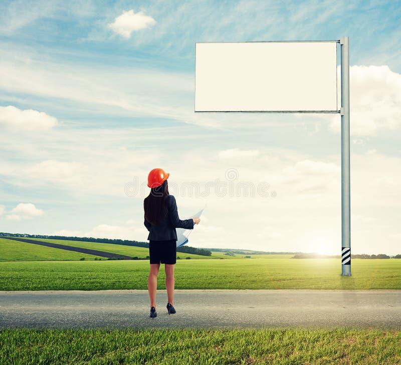 Γυναίκα που εξετάζει τον κενό μεγάλο πίνακα διαφημίσεων στοκ φωτογραφίες με δικαίωμα ελεύθερης χρήσης