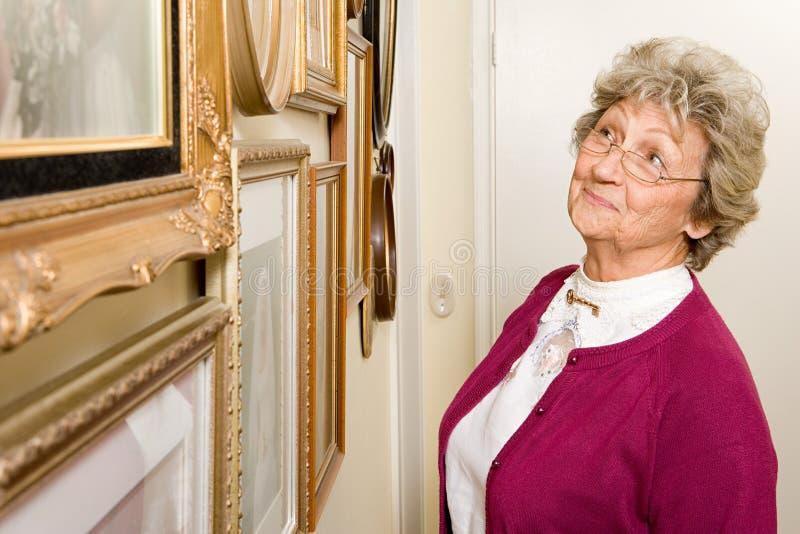 Γυναίκα που εξετάζει τον τοίχο των φωτογραφιών στοκ φωτογραφίες