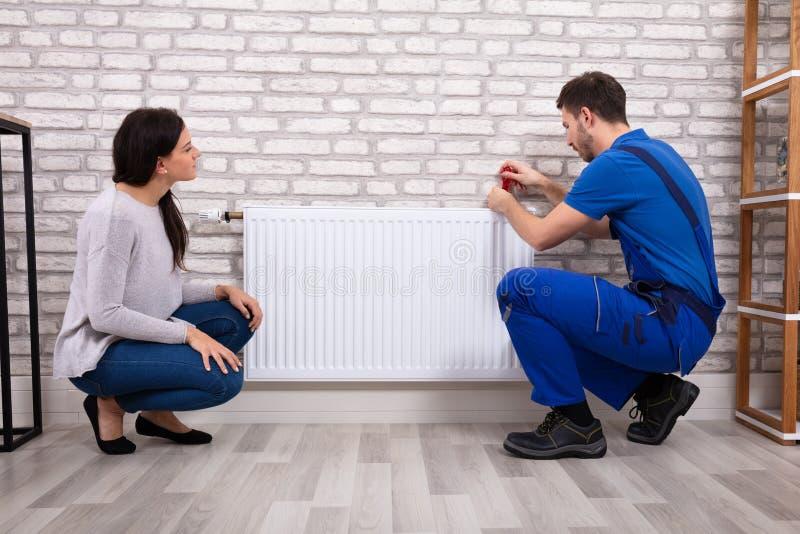 Γυναίκα που εξετάζει τον υδραυλικό που εγκαθιστά το θερμαντικό σώμα με το κατσαβίδι στοκ φωτογραφία με δικαίωμα ελεύθερης χρήσης