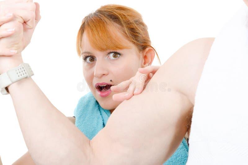 Γυναίκα που εξετάζει τους δικέφαλους μυς κάμψης του μυϊκού φίλου της στοκ φωτογραφία