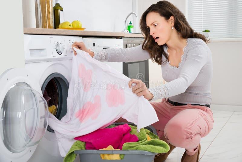 Γυναίκα που εξετάζει το λεκιασμένο ύφασμα στοκ εικόνα με δικαίωμα ελεύθερης χρήσης
