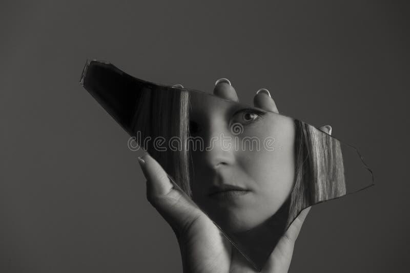Γυναίκα που εξετάζει το πρόσωπό της σε ένα shard του σπασμένου καθρέφτη καλλιτεχνικό γ στοκ φωτογραφία με δικαίωμα ελεύθερης χρήσης
