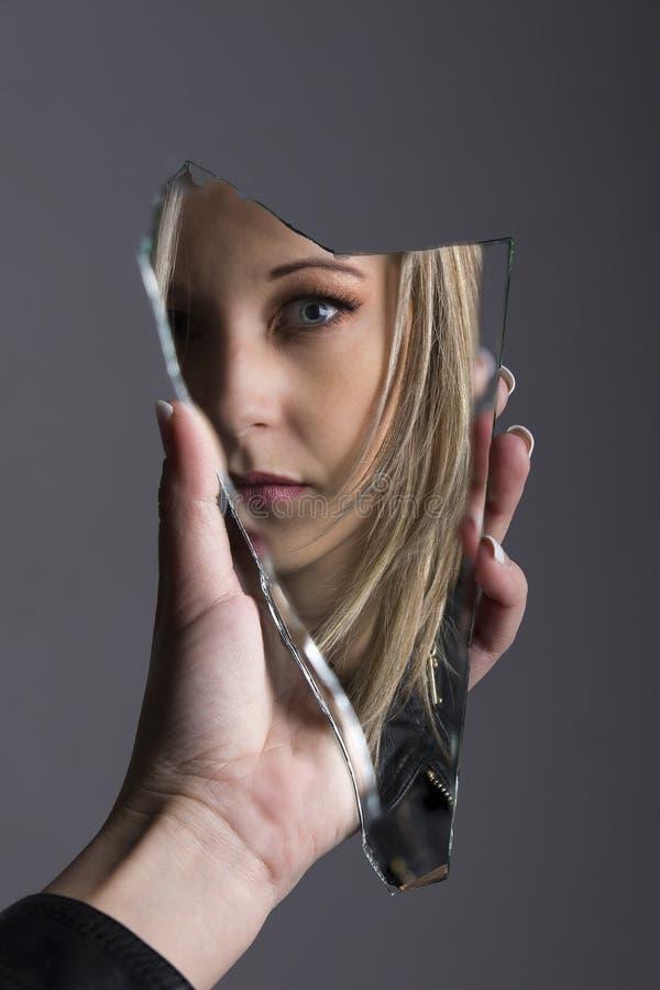 Γυναίκα που εξετάζει το πρόσωπό της στο shard του σπασμένου καθρέφτη στοκ φωτογραφία με δικαίωμα ελεύθερης χρήσης